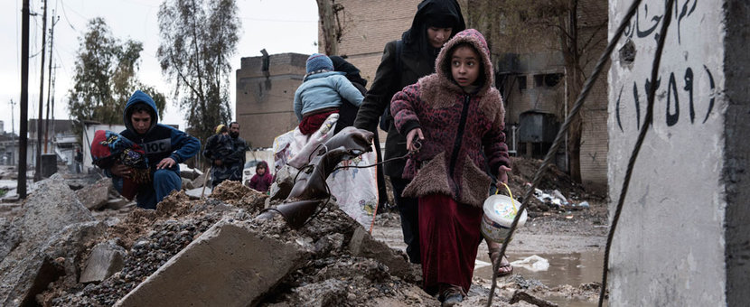 A family displaced by fighting between ISIS and Iraqi security forces carry their belongings as they walk through the destroyed western neighbourhood of Al Mamum, near Mosul, Iraq. Photo: UNICEF/Alessio Romenzi